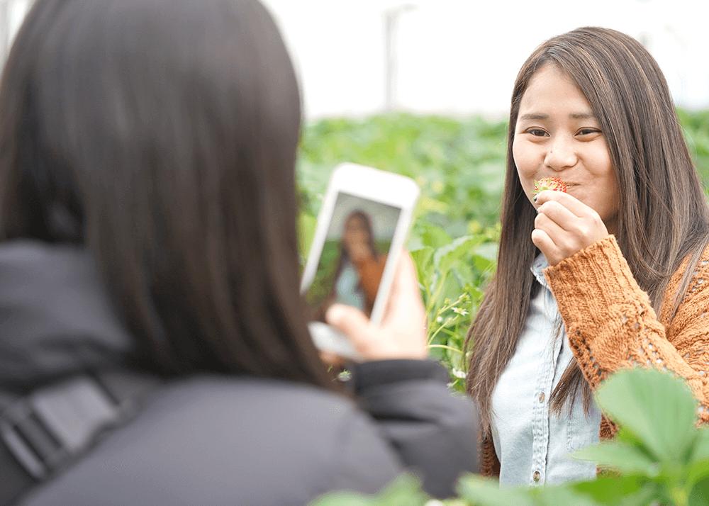 苺を頬張りながらスマホで撮影をする女性たち
